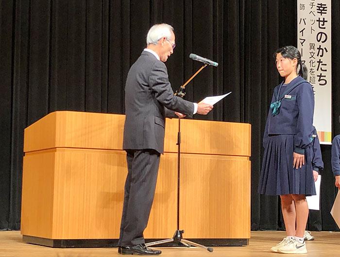 娘が市長から表彰場を受け取る