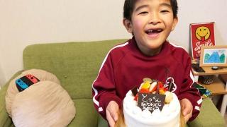 7歳の誕生日ケーキをもつ息子