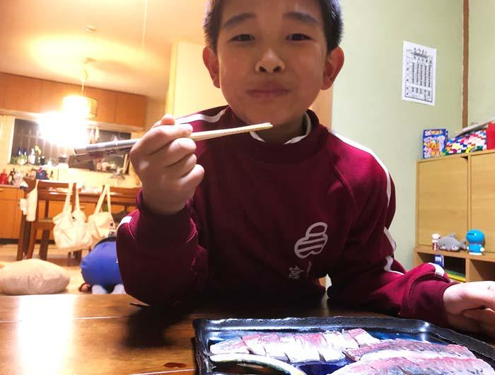 アジのお刺身を食べる息子