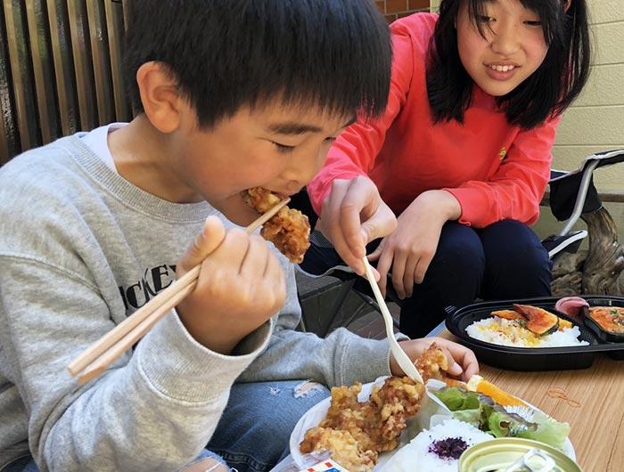 唐揚げ弁当を食べる姉弟