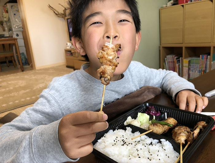 やきとり弁当を食べる息子