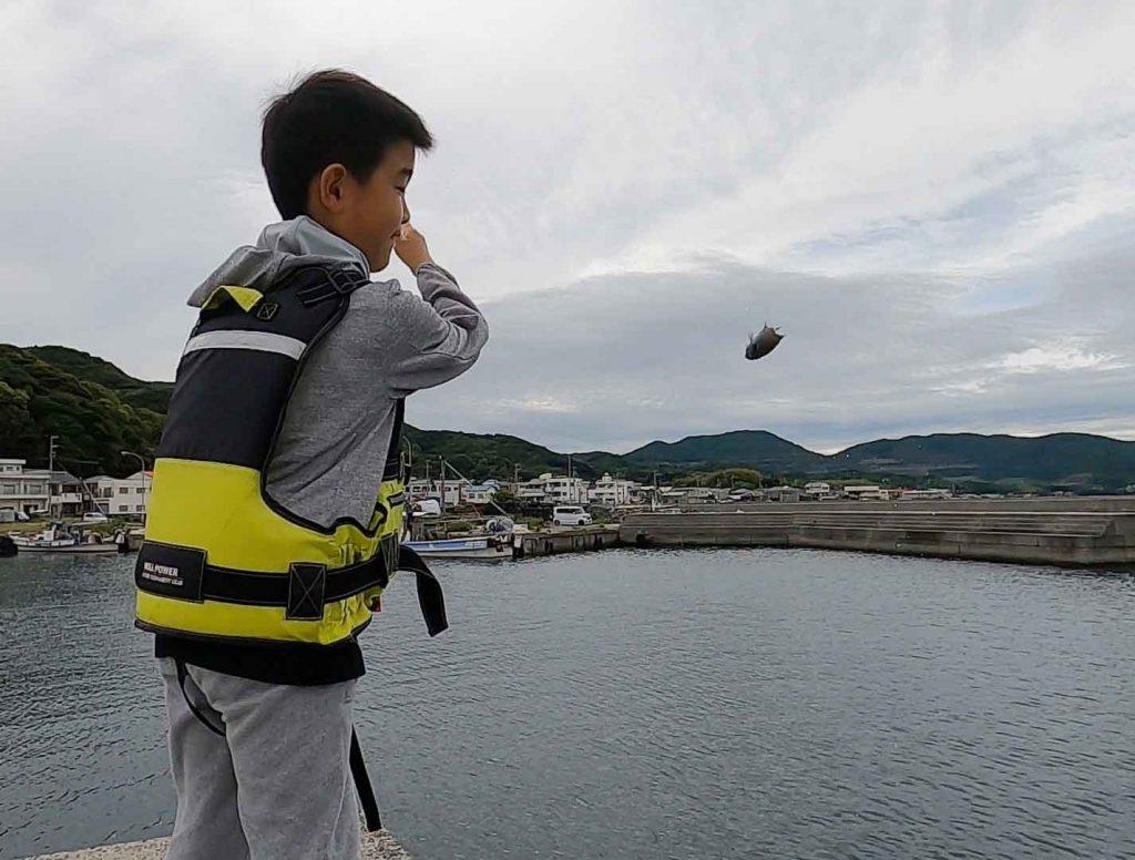 魚を投げる息子