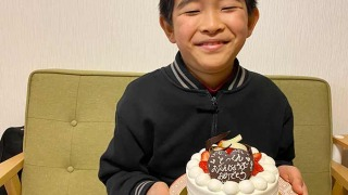 kukuluの誕生日ケーキを持つ息子