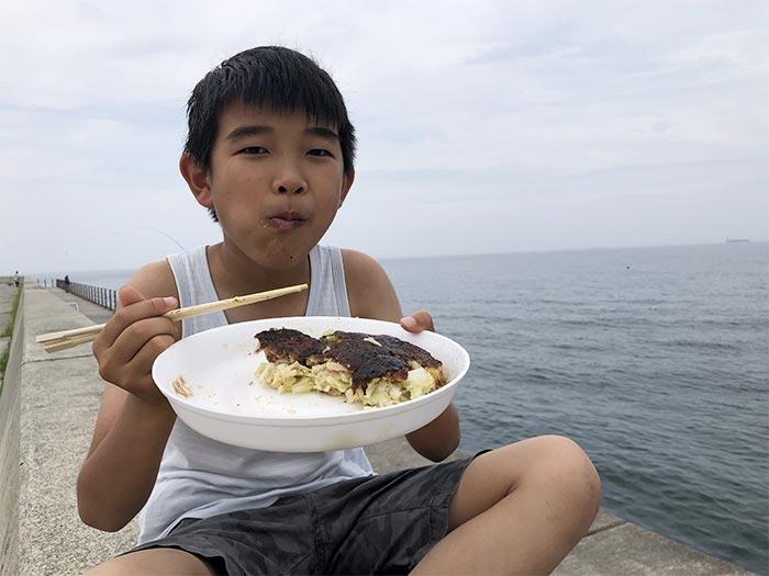 お好み焼きを海で食べる息子